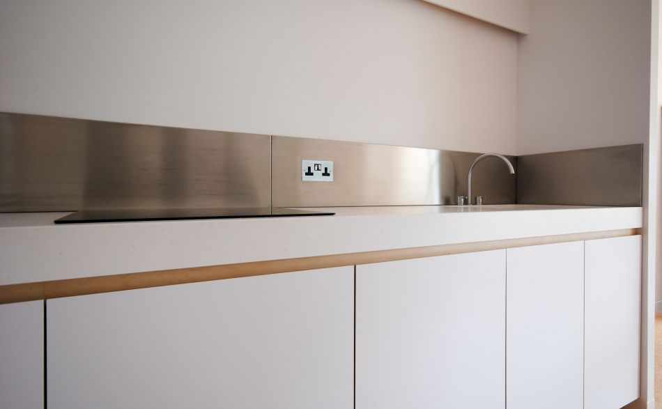 Corian kitchen worktop with stainless steel backspash and white cabinets