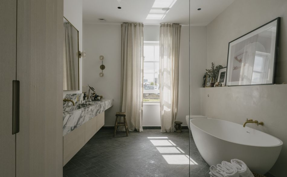 Bathroom with white bath and marble vanity