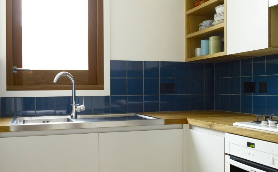 Kitchen with window over sink and blue tiles