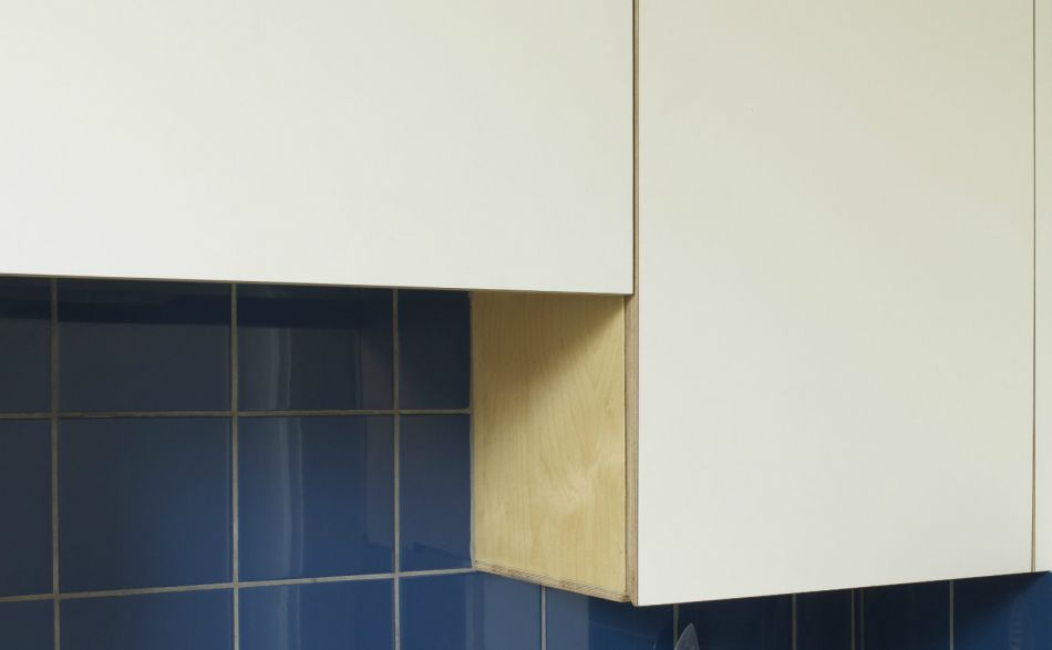 Simple white laminate kitchen cupboards with deep blue ceramic tiles
