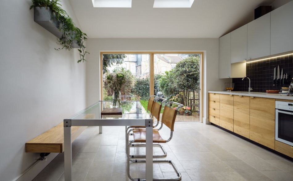 bright kitchen with skylights, hanging plants and a large dining table