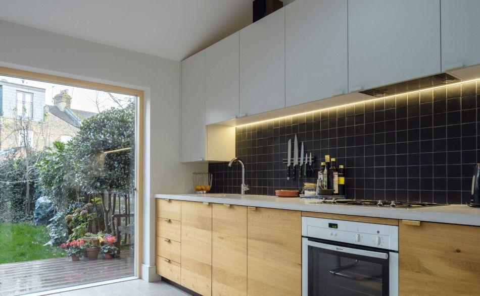 modern kitchen leading into large doors overlooking the garden