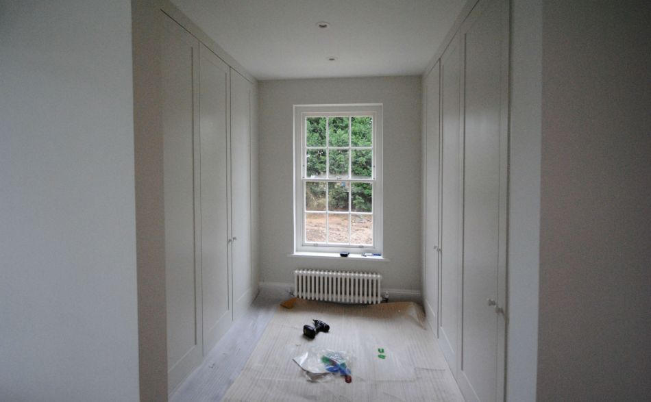 Walk-in wardrobe or dressing room with traditional solid wood panelled doors