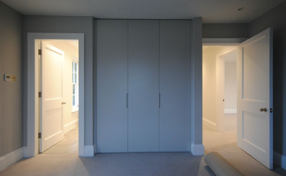 A modern full-height white wardrobe fitted between two bedroom doors
