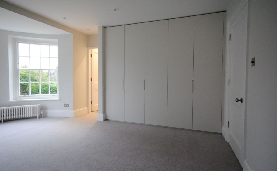Full height fitted white wardrobes in a traditional London home