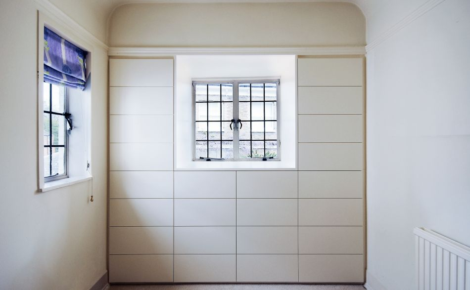 Room with a wall of storage surrounding a leaded glass window